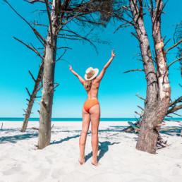 Dziewczyna na plaży w Juracie w pomarańczowym kostiumie i kapeluszu