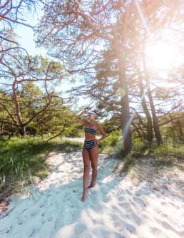 Kobieta w kostiumie kąpielowym w paski nad morzem bałtyckim