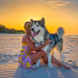 kobieta z psem na plaży zachód słońca