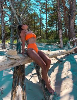 Kobieta w pomarańczowym kostiumie dwuczęściowym na plaży w Juracie