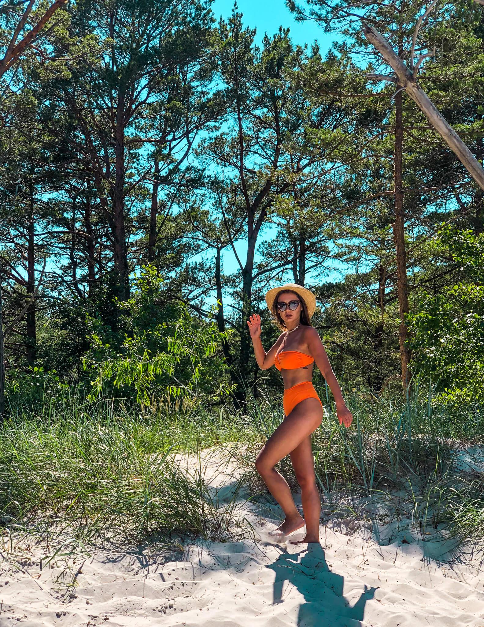 Kobieta w pomarańczowym stroju kąpielowym nad morzem